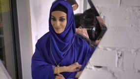 Mujer musulmán hermosa joven en el hijab que intenta en la pulsera en joyería, considerando y sonriendo la reflexión en espejo almacen de video