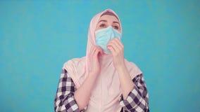 Mujer musulmán hermosa joven en máscara médica que tose, espasmo almacen de video