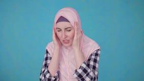 Mujer musulmán hermosa joven que experimenta jaqueca severa del dolor de cabeza almacen de metraje de vídeo