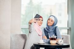 Mujer musulmán hermosa joven que toma un autorretrato con el teléfono de la cámara Imágenes de archivo libres de regalías