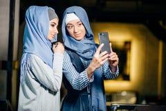 Mujer musulmán hermosa joven que toma un autorretrato con el teléfono de la cámara Imagen de archivo libre de regalías