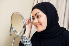 Mujer musulmán hermosa que aplica el rimel Mujer árabe joven que usa el cepillo del latigazo foto de archivo libre de regalías