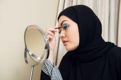 Mujer musulmán hermosa que aplica el rimel Mujer árabe joven que usa el cepillo del latigazo imagen de archivo libre de regalías