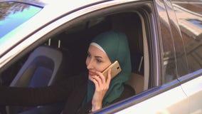 Mujer musulmán hermosa que conduce un coche que habla en la sonrisa del teléfono fotografía de archivo libre de regalías