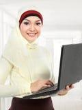 Mujer musulmán joven asiática en la bufanda principal usando el ordenador portátil Fotos de archivo