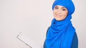 Mujer musulmán joven con el tablero metrajes