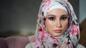 Mujer musulmán joven con los ojos pintados en hijab, miradas en la cámara y centelleos lentamente metrajes