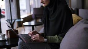 Mujer musulm?n joven concentrada que trabaja en el ordenador port?til moderno en caf? Mujer atractiva en el hijab que sostiene el metrajes