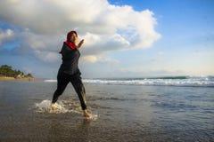 Mujer musulmán joven del corredor sano y activo en la bufanda principal del hijab del Islam que corre y que activa en la playa qu fotos de archivo libres de regalías