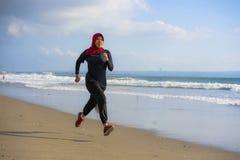 Mujer musulmán joven del corredor sano y activo en la bufanda principal del hijab del Islam que corre y que activa en la playa qu imagenes de archivo