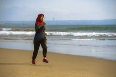 Mujer musulmán joven del corredor sano y activo en la bufanda principal del hijab del Islam que corre y que activa en la playa qu imagen de archivo libre de regalías