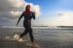 Mujer musulmán joven del corredor sano y activo en la bufanda principal del hijab del Islam que corre y que activa en la playa qu fotos de archivo