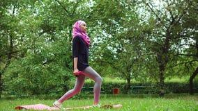Mujer musulmán joven en burqa que se agacha con pesas de gimnasia en parque del verano almacen de video