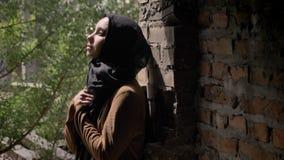 Mujer musulmán joven en el hijab negro que lleva a cabo sus manos y que mira hacia arriba, colocándose en el edificio de ladrillo almacen de video