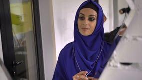 Mujer musulmán joven en el hijab que intenta en el collar y la pulsera en la joyería, mirando la reflexión en espejo metrajes