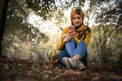 Mujer musulmán joven en parque de la ciudad fotos de archivo