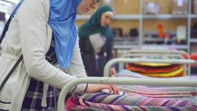 Mujer musulmán joven en tienda de la alfombra almacen de video