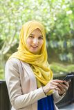 Mujer musulmán joven feliz que sostiene un teléfono mientras que mira hacia fuera Fotos de archivo