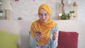 Mujer musulmán joven positiva en hijab que sonríe sosteniendo smartphone y tarjeta de banco que se sienta en el sofá en sala de e almacen de video