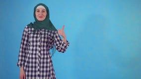 Mujer musulmán joven que muestra los pulgares para arriba en un fondo azul almacen de video