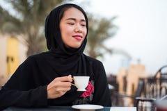 Mujer musulmán que come una taza de café al aire libre Imágenes de archivo libres de regalías