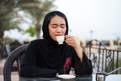 Mujer musulmán que come una taza de café al aire libre Foto de archivo libre de regalías