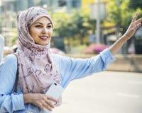 Mujer musulmán que espera un taxi Fotos de archivo libres de regalías