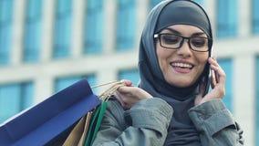 Mujer musulmán que habla con el amigo en el smartphone, jactándose de compras, primer almacen de video
