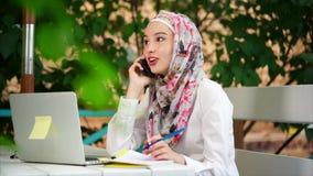 Mujer musulmán que hace llamada de teléfono del negocio