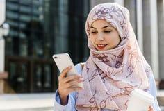 Mujer musulmán que juega con su móvil Imagen de archivo libre de regalías