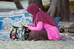 Mujer musulmán que juega el dispositivo del teléfono Foto de archivo libre de regalías