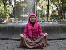 Mujer musulmán que medita en el parque imagenes de archivo
