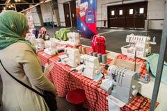 Mujer musulmán que mira las máquinas de coser Fotografía de archivo