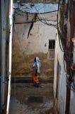 Mujer musulmán que recorre a través de las calles estrechas imagen de archivo