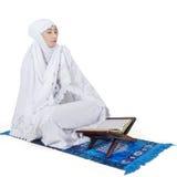 Mujer musulmán que ruega con Corán Imagenes de archivo