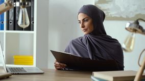Mujer musulmán que trabaja con los documentos metrajes
