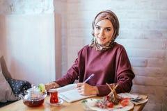 Mujer musulmán que trabaja en café Imagen de archivo libre de regalías