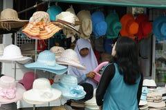 Mujer musulmán que vende los sombreros Imagen de archivo libre de regalías