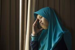 Mujer musulmán triste y deprimida en la ventana tradicional de la bufanda de la cabeza de Hijab del Islam en casa que siente cris imagen de archivo