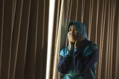 Mujer musulmán triste y deprimida joven en la ventana tradicional de la bufanda de la cabeza de Hijab del Islam en casa que sient imagen de archivo libre de regalías