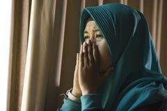 Mujer musulmán triste y deprimida joven en la ventana tradicional de la bufanda de la cabeza de Hijab del Islam en casa que sient imagen de archivo