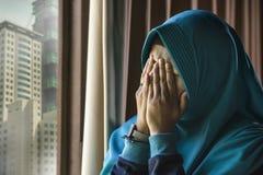 Mujer musulmán triste y deprimida joven en la ventana tradicional de la bufanda de la cabeza de Hijab del Islam en casa que sient imágenes de archivo libres de regalías