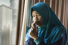 Mujer musulmán triste y deprimida joven en la ventana tradicional de la bufanda de la cabeza de Hijab del Islam en casa que sient fotos de archivo
