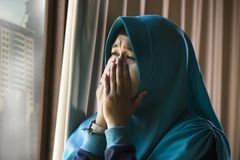 Mujer musulmán triste y deprimida joven en la ventana tradicional de la bufanda de la cabeza de Hijab del Islam en casa que sient fotografía de archivo libre de regalías