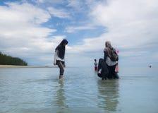Mujer musulm?n en el destino Halal del turismo, la playa y el oc?ano azul fotografía de archivo