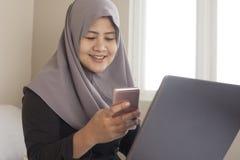 Mujer musulm?n feliz que trabaja con el ordenador port?til y el tel?fono elegante en su dormitorio imagenes de archivo