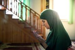 Mujer musulm?n joven que ruega en la mezquita imagen de archivo libre de regalías