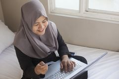 Mujer musulm?n que hace la compra en l?nea fotos de archivo
