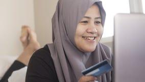 Mujer musulm?n que hace la compra en l?nea fotografía de archivo libre de regalías