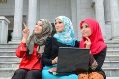 Mujer musulmán asiática joven en la bufanda principal con el ordenador portátil Imagenes de archivo